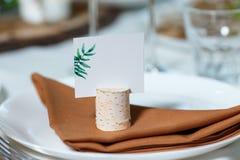 Ajuste de la tabla de la boda con la tarjeta en blanco de la huésped en un plato De rústico imágenes de archivo libres de regalías