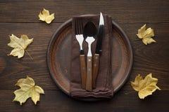 Ajuste de la tabla de la caída para la cena de la acción de gracias en la tabla de madera rústica con las hojas de arce amarillas Imagen de archivo
