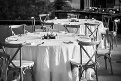 Ajuste de la tabla de cena de la recepción nupcial con las sillas de jardín plegables en blanco y negro Imagen de archivo libre de regalías
