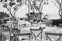 Ajuste de la tabla de cena de la recepción nupcial con las sillas de jardín plegables en blanco y negro Fotografía de archivo libre de regalías