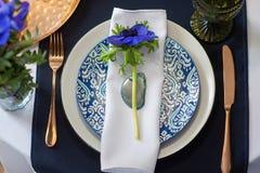 Ajuste de la tabla con las anémonas azules Imagen de archivo