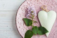 Ajuste de la tabla con las flores del corazón y de la lila Imágenes de archivo libres de regalías