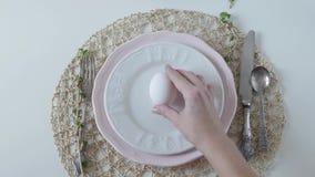 Ajuste de la tabla con los platos blancos en el fondo blanco el huevo hervido para las manos femeninas del desayuno pone un huevo almacen de metraje de vídeo