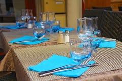 Ajuste de la tabla - cuchillo y bifurcación, cubiletes de cristal, servilletas azules en b fotos de archivo
