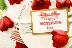 Ajuste de la tabla de cena con la tarjeta y los tulipanes del mensaje del día de madres Foto de archivo