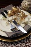 Ajuste de la tabla de cena de la Navidad del tema del oro. Ciérrese para arriba en los cubiertos y las placas Fotografía de archivo