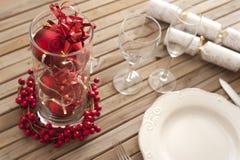 Ajuste de la tabla de la Navidad con las decoraciones rojas Fotografía de archivo libre de regalías