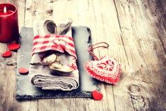 Ajuste de la tabla de la tarjeta del día de San Valentín del St en tono rojo en la tabla de madera vieja Foto de archivo libre de regalías