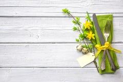 Ajuste de la tabla de Pascua con el narciso y los cubiertos Imagenes de archivo