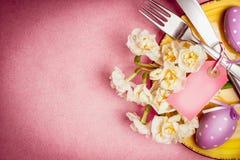 Ajuste de la tabla de Pascua con la placa, los cubiertos, las flores, los huevos y la etiqueta en blanco en el fondo rosado, visi Imagenes de archivo