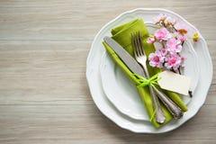 Ajuste de la tabla de Pascua con las flores y los cubiertos de la primavera Fotos de archivo