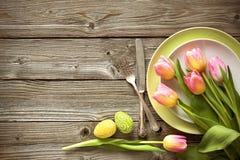 Ajuste de la tabla de Pascua con los tulipanes y los cubiertos de la primavera imagen de archivo