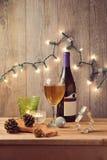 Ajuste de la tabla del día de fiesta de la Navidad con el vino y las luces de la Navidad Foto de archivo