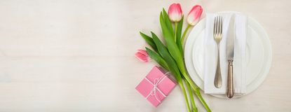 Ajuste de la tabla del día de tarjetas del día de San Valentín con tulipanes rosados y un regalo en el fondo de madera blanco Vis Imágenes de archivo libres de regalías