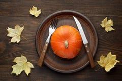 Ajuste de la tabla del otoño con la calabaza y los cubiertos en la placa en fondo de madera con las hojas de arce Foto de archivo