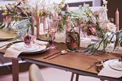 Ajuste de la tabla en color rosado, para una boda u otro acontecimiento, copas de vino, placas, cucharas, bifurcaciones, flores y imagen de archivo