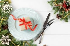 Ajuste de la tabla de Navidad con el regalo en la placa en la tabla blanca Fotografía de archivo libre de regalías