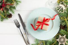 Ajuste de la tabla de la Navidad con el regalo en la placa en la tabla de madera blanca Fotografía de archivo libre de regalías