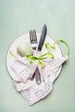 Ajuste de lugar da tabela da Páscoa com a decoração da cutelaria e do ovo na luz - fundo verde fotografia de stock royalty free