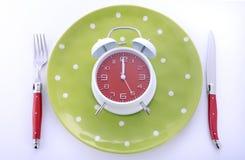 Ajuste de lugar da tabela das horas de comer com despertador Foto de Stock