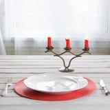 Ajuste de lugar da tabela do feriado com dishware branco, cutelaria, pratas e as decorações vermelhas na placa de madeira branca  Imagens de Stock Royalty Free