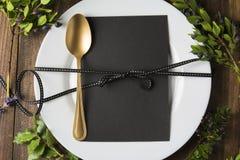 Ajuste de lugar do menu com cartão vazio e colher dourada sobre o fundo de madeira, cercado por ramos verdes Imagem de Stock Royalty Free