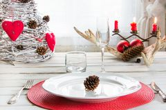 Ajuste de lugar do Natal com dishware branco, pratas e as decorações vermelhas na placa branca no interior perto da janela Imagens de Stock Royalty Free
