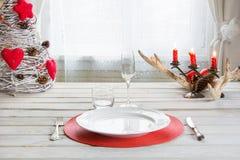 Ajuste de lugar do Natal com dishware, a pratas e as decorações brancos na placa branca no interior perto da janela Imagem de Stock Royalty Free
