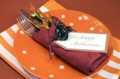Ajuste de lugar feliz da tabela de Dia das Bruxas com às bolinhas e placa e guardanapo alaranjados da listra Foto de Stock