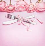 Ajuste de lugar romântico da tabela com as flores, a cutelaria e a fita cor-de-rosa das rosas Casamento, convite, data ou cartão fotografia de stock royalty free
