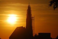 Ajuste de Sun atrás da torre de igreja coberta com o andaime Foto de Stock