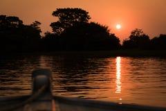 Ajuste de Sun atrás das árvores mostradas em silhueta do barco Fotos de Stock Royalty Free