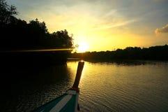 Ajuste de Sun atrás das árvores mostradas em silhueta do barco Foto de Stock Royalty Free