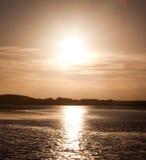 Ajuste de Sun sobre a água Imagens de Stock Royalty Free