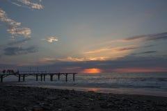 Ajuste de Sun sobre a doca ou o cais do terraço Mar do molhe e fundo do céu nebuloso, por do sol fotos de stock royalty free