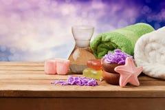 Ajuste del balneario con el jabón y las toallas en la tabla de madera sobre fondo del bokeh Fotografía de archivo libre de regalías