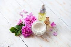 Ajuste del balneario con el pote de rosas rosadas hermosas poner crema hidratantes y de aceite color de rosa en el fondo blanco Fotos de archivo libres de regalías