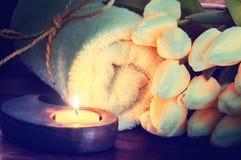 Ajuste del balneario con la toalla, la vela y las flores Imagenes de archivo