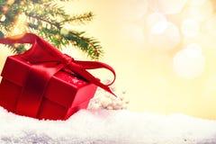 Ajuste del día de fiesta de la Navidad con el presente en caja roja sobre nieve Imagenes de archivo