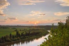 Ajuste del resplandor solar sobre el río de los ciervos comunes Imagenes de archivo