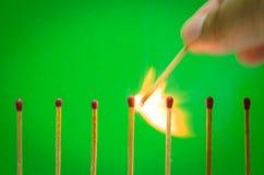 Ajuste do fósforo de Burnning no fundo verde para ideias e inspira Imagens de Stock Royalty Free