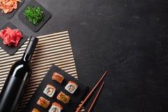 Ajuste do sushi e do maki com uma garrafa do vinho na tabela de pedra Vista superior imagens de stock royalty free