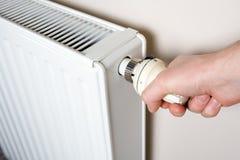 Ajuste do termostato pela mão do homem Foto de Stock