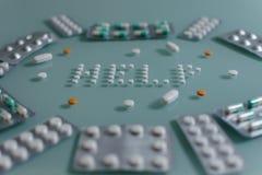 Ajuste dos comprimidos fracos e das tabuletas completas na tabela de vidro verde imagem de stock