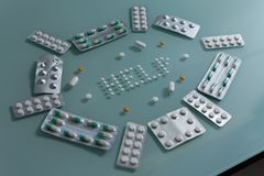 Ajuste dos comprimidos fracos e das tabuletas completas na tabela de vidro verde fotos de stock royalty free