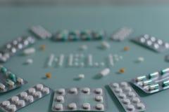 Ajuste dos comprimidos fracos e das tabuletas completas na tabela de vidro verde imagem de stock royalty free