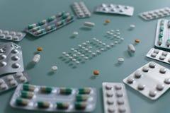 Ajuste dos comprimidos fracos e das tabuletas completas na tabela de vidro verde fotografia de stock royalty free