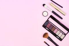 Ajuste dos cosméticos decorativos no fundo cor-de-rosa pastel Espa?o para o texto fotografia de stock