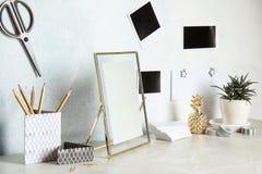 Ajuste dos elementos decorativos diferentes na tabela contra a parede da cor fotografia de stock