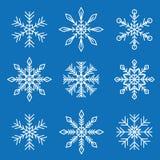 Ajuste dos flocos de neve diferentes brancos isolados no fundo azul ilustração royalty free